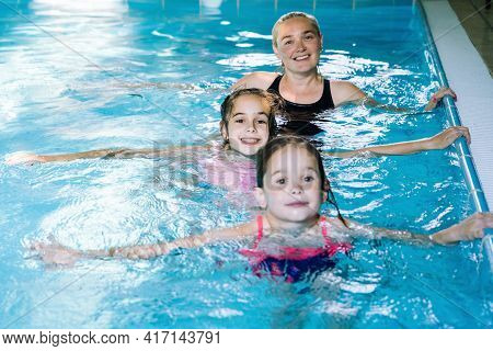 Mother With Two Daughters Having Fun In Indoor Swimming-pool. Girl Is Resting At The Water Park. Swi