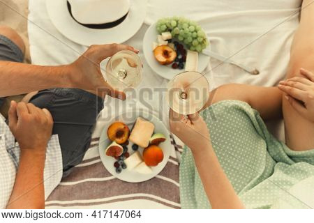 Top View Of Anonymous Man And Woman With Wineglasses Proposing Toast Over Fruits During Romantic Pic