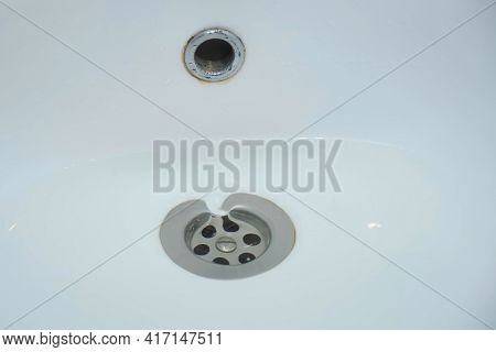 Water Is Draining In Drain Hole Of The Sink In Bathroom, Closeup View. Bath Clogging And Repairing C