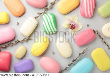 Different White Soaps With Flowers. A Lot Of Solid Soap For Hygiene And Cleanliness On A Grey Backgr