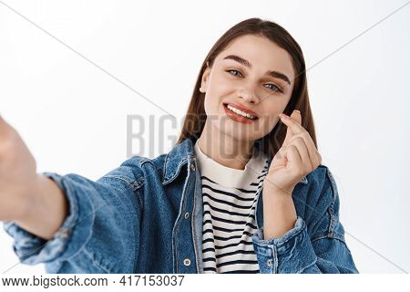Close Up Of Young Gen-z Girl Takes Selfie On Smartphone, Holds Phone And Shows Finger Heart Korean G