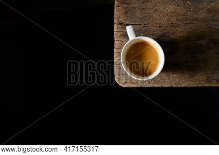 Conceptual Espresso Cup With Shadow On Wooden Table
