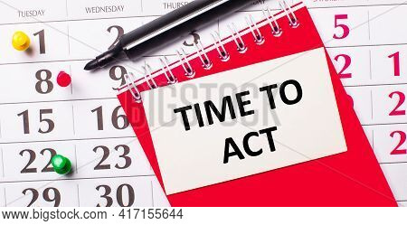 On The Calendar Is A White Card With The Text Time To Act. Nearby Is A Red Notepad And A Marker. Vie