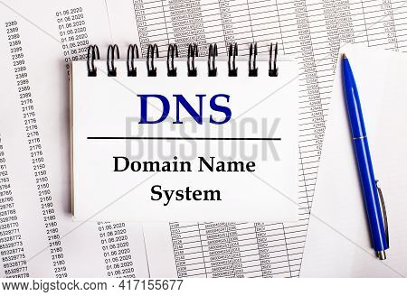 On The Table Are Charts And Reports, On Which Lie A Blue Pen And A Notebook With The Word Dns Domain