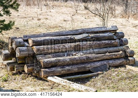 A Pile Of Old Rotten Logs Piled On The Ground In The Open Air. Logs From An Old Disassembled House P