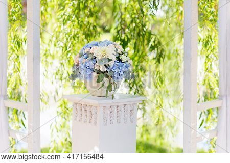 Flower Arrangement With Hydrangeas, Roses, Dahlias, Eucalyptus Trees In A Flower Pot On A Wooden Ped