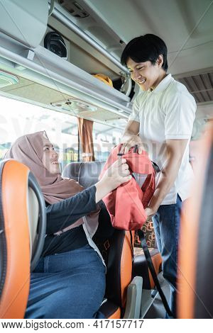 A Young Man Helps A Veiled Woman Put Her Bag On A Shelf
