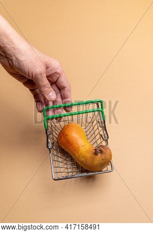 Woman Hand Reaching For Ugly Pear In Small Supermarket Shopping Basket On Beige Background.