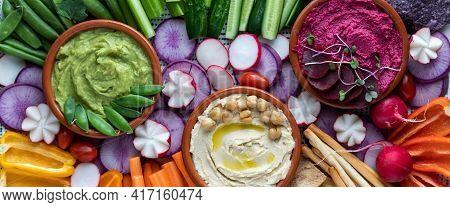 Narrow Close Up View Of Three Dips Surrounded By Fresh Cut Vegetables For Dipping.