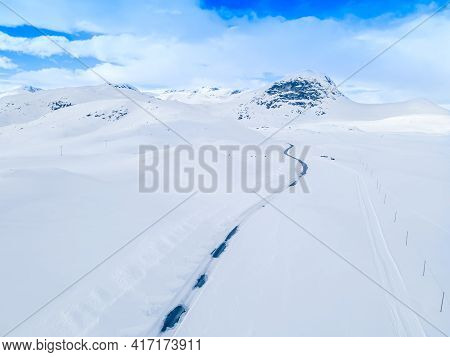 Lonely Frozen Road Winding Through A Snow Covered Mountain Landscape On A Cold Winters Day.