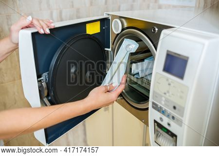 The Dental Assistant Takes The Disinfected Instrument Out Of The Sterilizer. Sterile Dental Instrume
