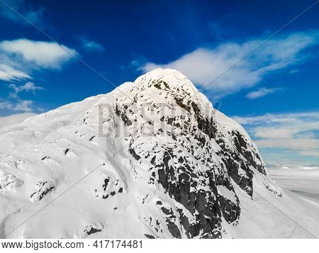 Panoramic View Of A Snow Capped Mountain Peak With Clouds And Blue Skies. Mount Bitihorn In Norway.