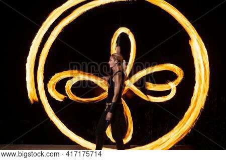 Firedancer. Sexy Woman Perform Fire Tricks In Darkness. Fire Performance. Burning Poi Spinning.
