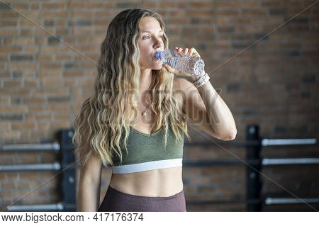 Fitness Woman Holding A Bottle Of Water After Workout At The Gym. Sporty Attractive Woman In Sportsw