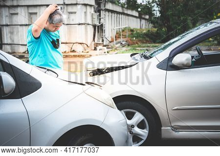 An Asian Middle-aged Man Is Under Stress From Accident Car Crash, Where He Is Watching The Damage Ca