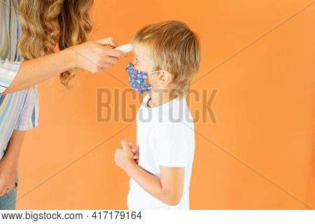 Pandemia Time And Health Concept, Mom Measuring Temperature To Her Son With Contactless Temometr, Fa