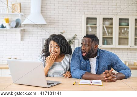 Overjoyed Young Multiracial Family Couple Looking At The Laptop Monitor, Feeling Excited Of Getting