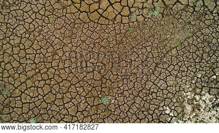 Top View Of Arid Surface Of Earth. Shot. Arid Terrain With Clay Soil And Sparse Grasses. Textured Su