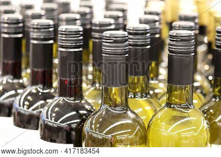 Wine Bottles In A Row, Selective Focus. Liquor Store, White And Red Wine Production Concept