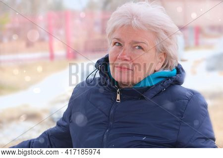 Pensive Attractive Mature Woman With  Blond Hair With A Quiet Smile As She Stands On An Outdoor Walk