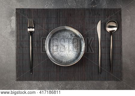 Empty Black Clay Plate And Sblack Metal Silverware Set On Wooden Table