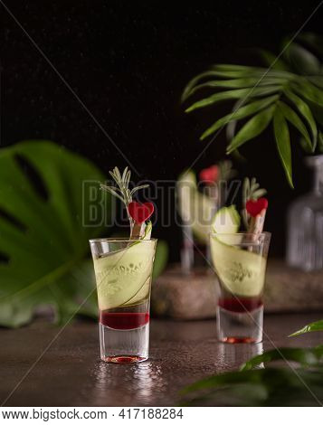 Layered Shots With Red Grenadine And Vodka Decorated With Slices Of Cucumber, Fresh Rosemary And Red