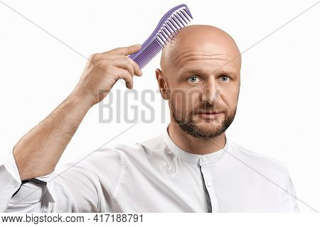 Hair Loss Concept. Young Bald Man With A Hairbrush On A White Background.