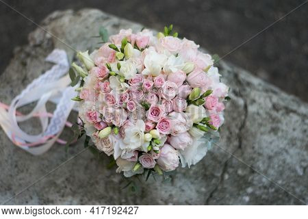 Beautiful Bridal Bouquet Of White And Pink Flowers And Greenery, Decorated With Long Silk Ribbon Lie