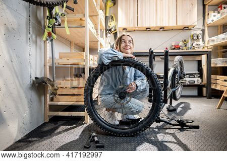 Portrait Of A Young Handywoman Reparing Her Bicycle In The Beautiful Small Workshop At Home. Diy Con