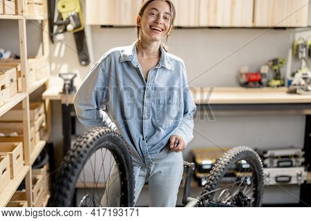 Young Handywoman Reparing Her Bicycle In The Beautiful Small Workshop At Home. Diy Concept
