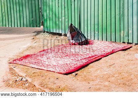 Homeless's Blanket And Black Plastic Bag Lays On The Ground Near Green Fence. Bed. Bedroom. Place To