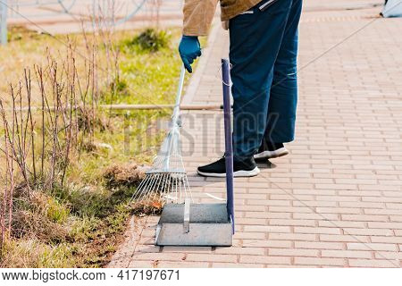 Metallic Scoop Stands On The Ground While Janitor Man Sweeps The Pavement With An Iron Broom On The