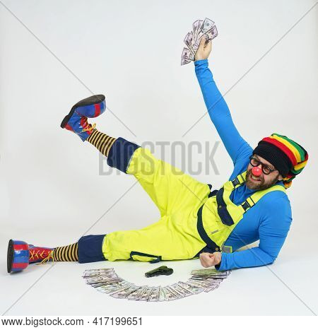 Humor And Fun Concept. A Clown In A Bright Costume Sits On The Floor And Holds Money In His Hands. N