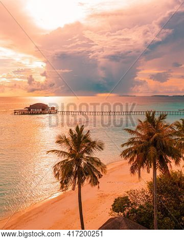 Wooden Pier Leading To The Island At Sunrise Or Sunset In The Maldives, The Concept Of Luxury Travel