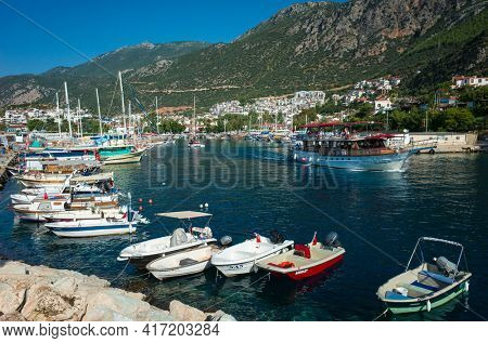 Kas, Turkey - 17 October, 2019: Boats in Kas Marina and mountains on Turkish Mediterranean coast, Popular tourist destination