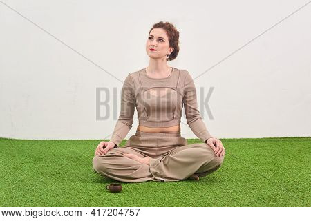 Young Woman Sitting In Lotus Position For Meditation And Looks Up Dreamily On Light Background