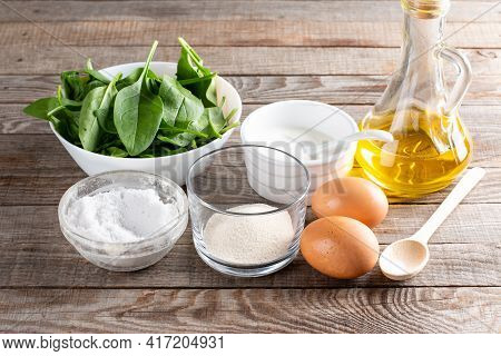 Set Of Raw Ingredients For Cooking Healthy Spinach Pancakes On Wooden Table (dough, Psyllium, Eggs,