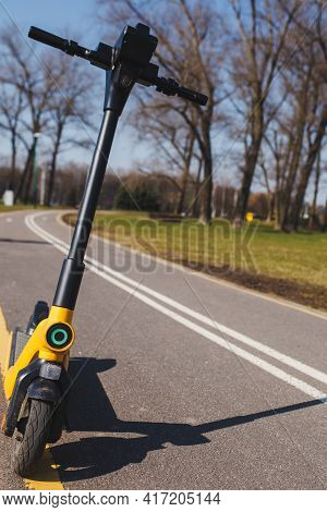 Yellow Electronic Scooter On The Road. Rental Of Scooters