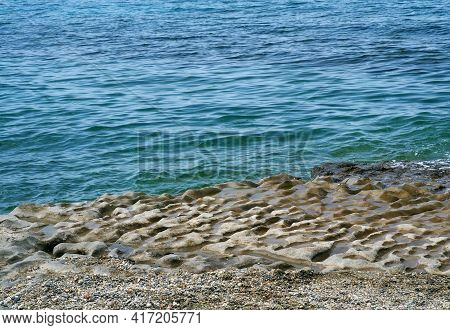 The Surface Of The Coastal Stone Is Uneven, Wavy. The Stone Is Worn Down By The Sea Waves. Natural L