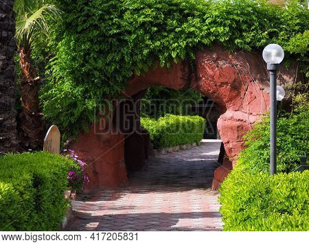 A Small Arched Tunnel From Above Is Overgrown With Bindweed. There Is A Lantern Near The Stone Arch,
