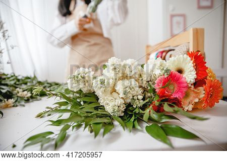The Florists Table Is Littered With Fresh Flowers Before Starting Work. Florist In The Background