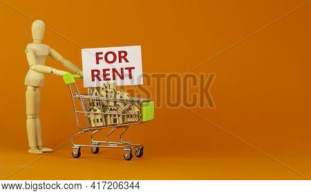 House For Rent Symbol. Miniature Shopping Cart With Wooden Houses, Words For Rent. Wooden Model Of H