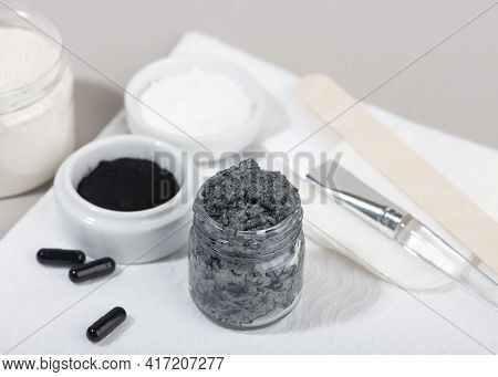 Ingredients For A Homemade Charcoal Facial Mask. Charcoal Powder, Coconut Oil, White Cosmetic Clay.
