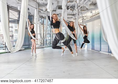 Group Of Female Are Doing Fly Yoga Exercises In Fitness Training White Gym Loft Classroom. Intense F