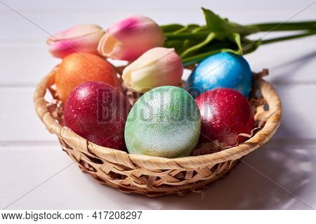 A Small Basket With Colorful Painted Eggs And A Bouquet Of Tulips On A White Wooden Background. Orth
