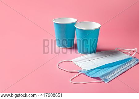 Disposable Paper Cup And Masks On A Pink Background. Disposable Tableware. Disposable Goods. Concept