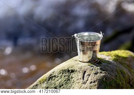 Aluminum Bucket With Water On The River Bank. Water Protection Concept. Close-up. Place For Your Tex