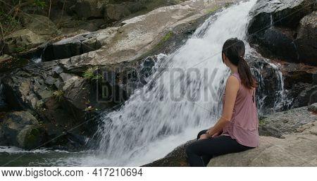 Sport woman sit beside waterfall