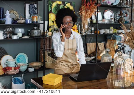 Afro Saleswoman Talking On Mobile And Typing On Laptop At Decor Shop. Various Beautiful Decor Lying