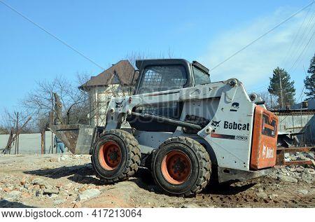 View Of Small Bulldozer. Construction machinery. Bulldozer on old house demolition. 24 March 2021. Kiev Region, Ukraine
